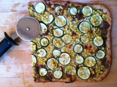 pizza topped with spicy pesto, fresh corn kernels, and thinly sliced zucchini