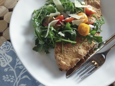 baked chicken cutlets topped with arugula, tomato, and onion salad